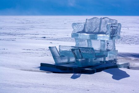 Sled from ice on a pedestal on the lake Baikal. Ice sculpture. The ice of the lake is covered with snow. Sunny. Horizontal.