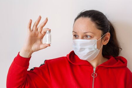 A girl in a medical mask holds in front of her a bottle of white powder in her hand and looks at it. European appearance. Long black hair. Red jacket with a zipper. White background. Horizontal.