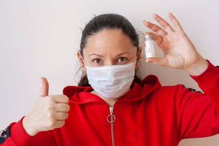 A young girl in a medical mask holds a medical bottle in her hand and shows a thumb up. European appearance. Long black hair. Red jacket with a zipper. White background. Horizontal.
