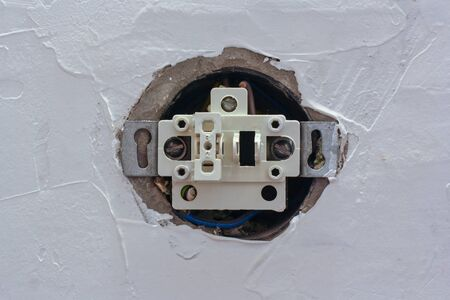 An electric switch with one button with the cover removed is recessed into the putty wall. Stages of construction. Horizontal.