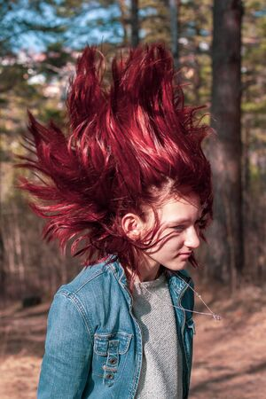 Stop-frame throwing back hair. Young girl with red hair stopped upstairs. Hair blurry in motion. Denim jacket and sweater. Blurred background with trees. Vertical.