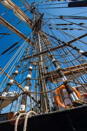 High mast with sails and rope ladders against the blue sky. Lifebuoy and lots of cables. Sails are assembled. Vertical.