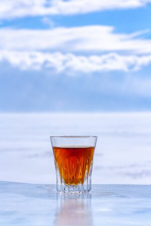 Whiskey in a glass stands on an ice surface on a blurry light background. Orange alcoholic drink in a glass. Copy space. Side view. Vertical. Stok Fotoğraf