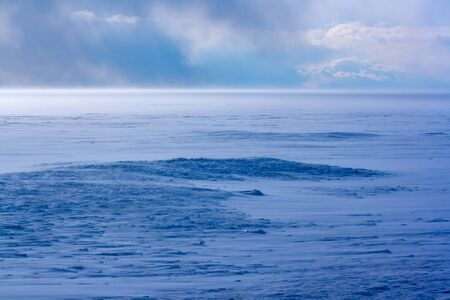 Blizzard on Lake Baikal in winter. Strong wind and a lot of snow. Blue shade of snow. Clouds in the sky. Horizontal.