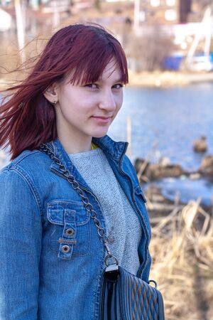 Portrait of a smiling teenage girl with red hair on a blurry background with a pond. Tricky facial expression. Jean jacket. Handbag over the shoulder. Vertical. Фото со стока