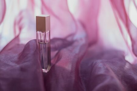 An elongated perfume bottle with pink airy fabric. Faceted glass vial. Wavy light fabric with waves. Blank for mock up. Copy space. Horizontal.