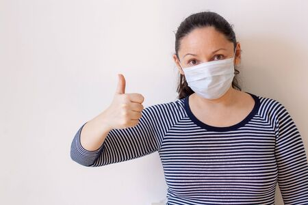 A girl in a medical mask shows thumb up on a white wall background with copy space. European appearance. Long black hair. Striped jacket. Focus on the face. Horizontal.