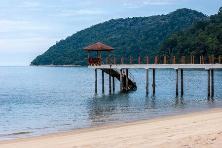 High mooring for stilt boats. Arbor with a roof. Sandy beach in the foreground. Cliffs overgrown with forest. Horizontal.