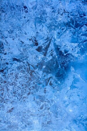 Amazing ice texture background. Blue ice lake with cracks and frozen air bubbles. Vertical.. Foto de archivo