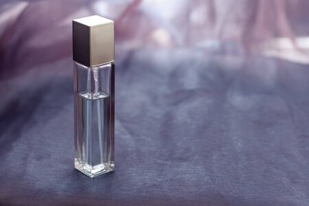 An elongated faceted perfume bottle with no inscriptions stands on the fabric. Glass vial with a metal cap. Blank for mock up. Shallow depth of field. Horizontal.