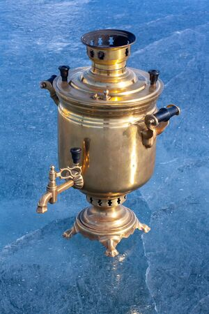 Retro samovar stands on the lake people. A Russian kettle works on firewood. Made of copper and brass. Cracks in the blue ice. Vertical.