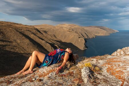 The girl lies on a rock above the lake. The model is wrapped in a scarf. In the background is a shore with beautiful cliffs. There are clouds in the sky.