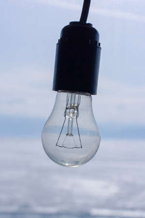 Old dusty incandescent lamp with a cartridge on a blurred background. The spiral is not damaged. Black cartridge and blue background. Vertical.