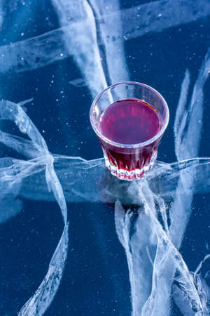 A glass with red tincture stands on the ice of the lake. Alcohol in a glass and ice with beautiful deep cracks. Vertical.