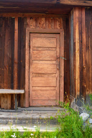 Old Russian door to the house with peeling paint and wooden steps. Vertical image.