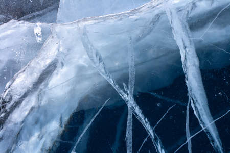 Deep crack in the thick ice of the lake. The natural texture of ice. Horizontal.