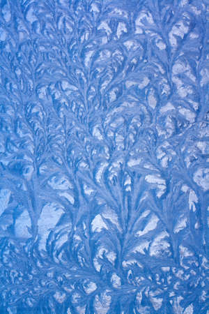 Nice frostwork. Gorgeous ice pattern on glass. Drawing on a frozen window. Vertical.