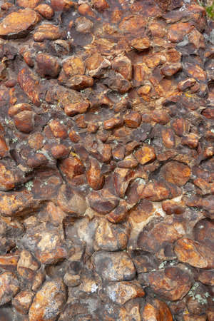 Background texture of surface of rock made of brown rounded stones. Vertical image. Standard-Bild