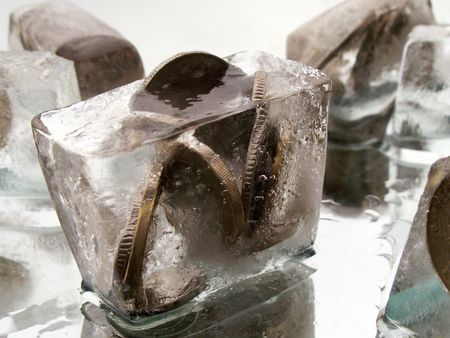 finanse: Coins inside pieces of ice on glass background with drops and water Stock Photo