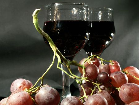 viticulture: Bunch of grapes and two wineglass on dark background Stock Photo