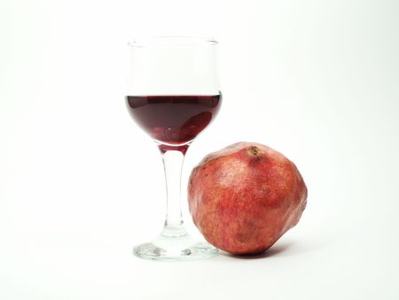bocal: One red pomegranate and bocal with red wine on white background