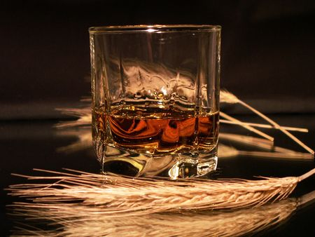 reverberation: Class of whisky and wheat ears on dark background