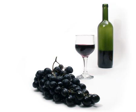 Wineglass and bunch of grapes on white background with green bottle photo