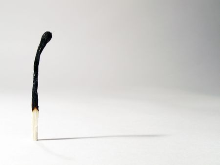 Lonely burnt match standing with its shadow on light-gray background
