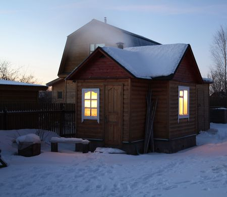 Little wooden house with glowing windows on winter evening photo