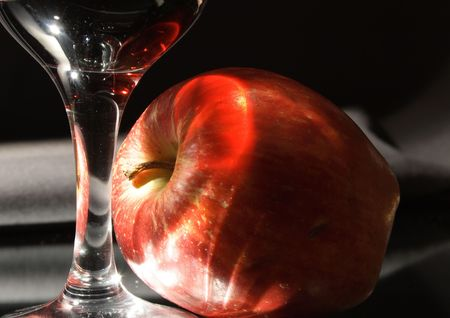 sensible: Wineglass and fresh red apple with lighting effects on dark gray