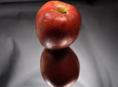 reverberation: Red apple on glass with its reverberation on light gray background
