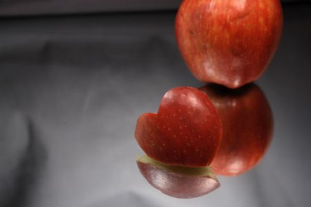 reverberation: Incised apple heart and red apple with reverberation on light gray Stock Photo