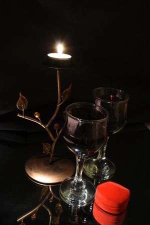 sensible: Two bocals of red wine and little red box as valentines present between its and candle