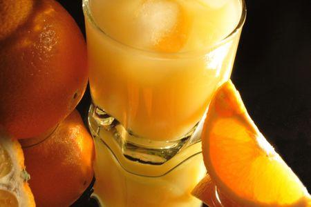 slit: Slit orange and glass of orange juice with ice on dark