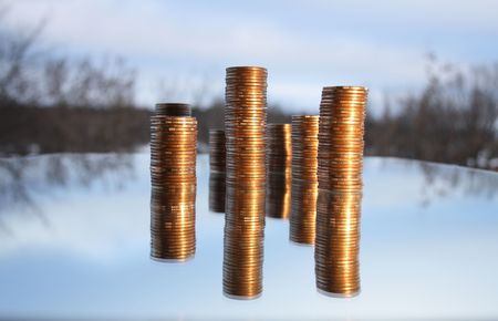 reverberation: Towers made from coins with reverberation on winter background Stock Photo