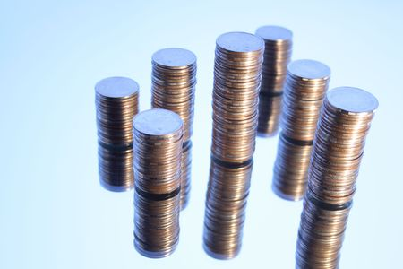 reverberation: Towers made from coins with reverberation on light-blue background Stock Photo