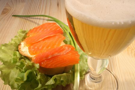 Fish Sandwich With Leaf Lettuce And Glass Of Beer On Wooden Table photo