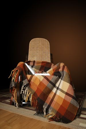 Rocking-chair with chequered plaid and open book on dark gradient background photo