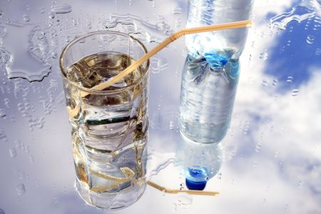 reverberation: Glass of mineral water with blebs on background with sky and bottle reverberation Stock Photo