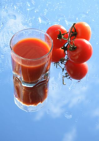 Glass of tomato juice on background with blue sky and three fresh tomatoes photo