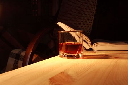 backgound: Glass of drink on wooden table on backgound with open book and home interior Stock Photo