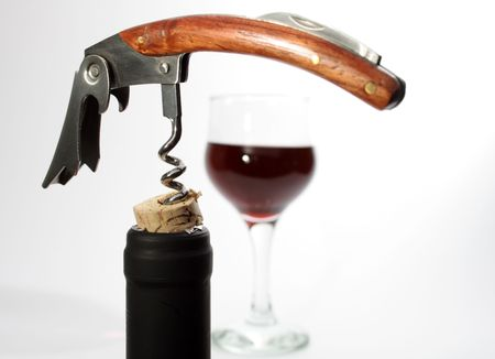 bottleneck: Black bottleneck with cork and nice corkscrew on background with wineglass