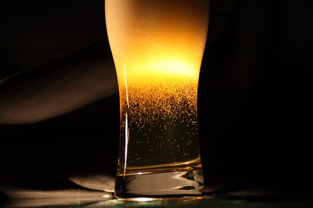 High glass of fresh beer with blebs and lot of foam on dark background