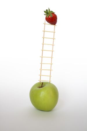 stilllife: Still-life with little wooden ladder between green apple and red strawberry