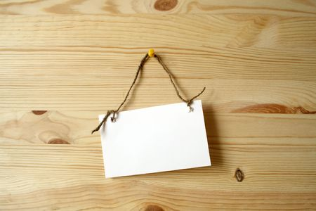 nameboard: White paper nameboard for notes hanging with rope on wooden background