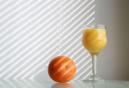 jalousie: Goblet of orange juice and fresh orange on glass table on background with jalousie shadow Stock Photo