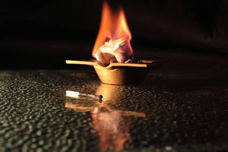bronzed: Burnt mutch lying on glass table on background with burning raper in bronzed ash-tray Stock Photo