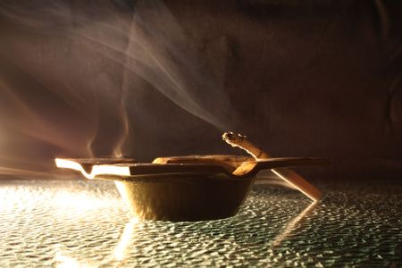 bronzy: Fuming cigarette with smoke lying on old bronzed ash-tray on dark background Stock Photo