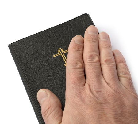 Male hand lying on the black leather-bound Bible on white background