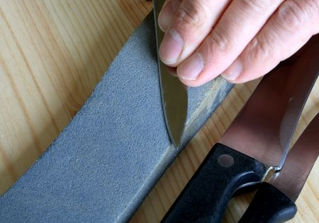 hone: Gray whetstone and kitchen knives on wooden background